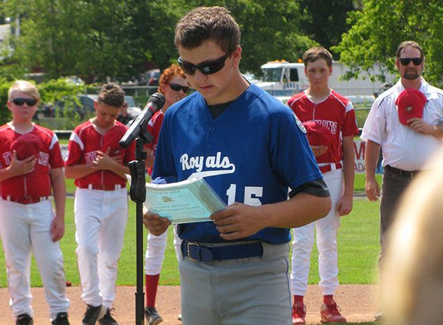Jesse Schutten giving the pledge at the pitchers mount with the players lined around the field.