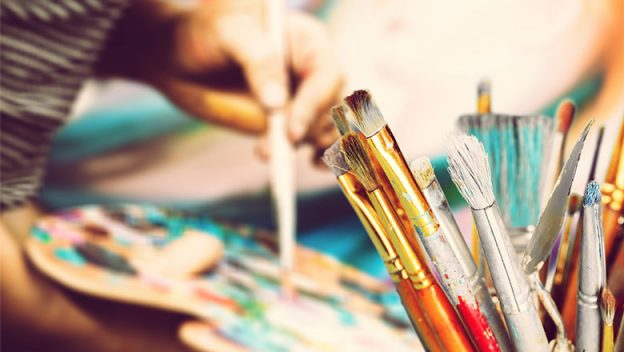 Paint brushes in the front with the hand of an artist holding a brush and paint pallet.