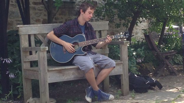 Austin Ritz playing guitar on a bench