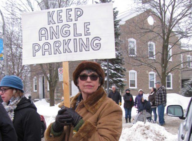 Jewel Brady holds up a KEEP ANGLE PARKING sign