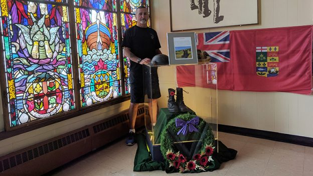 Hall of Remembrance Curator John Gemmell with the combat boots display outside the museum entrance.
