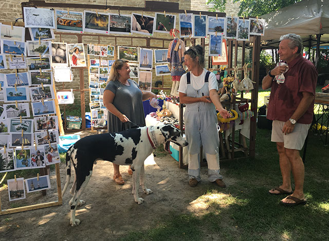 Woman holding her dog while talking to two other vendors.