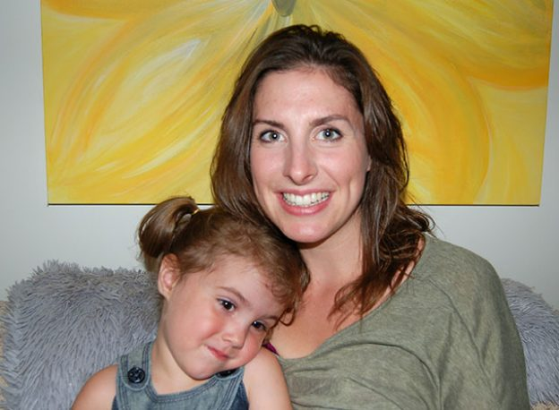 Devon Jacques with her daughter on her lap, sitting on a couch.