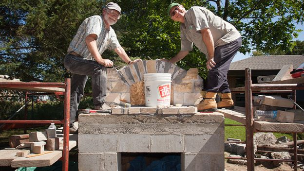 2 construction workers posting on top of a brick oven in the process of being built.