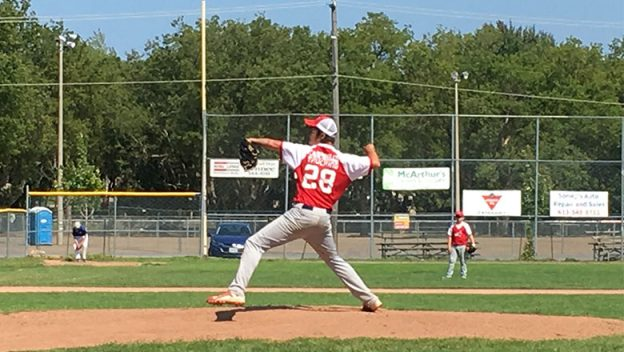Pitcher on the mound winding up to release the ball.