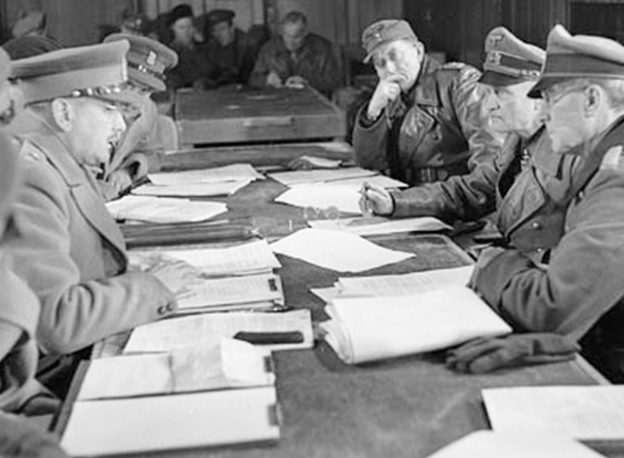 Charles Foulkes (left) faces General Paul Reichilt (right) during a conference