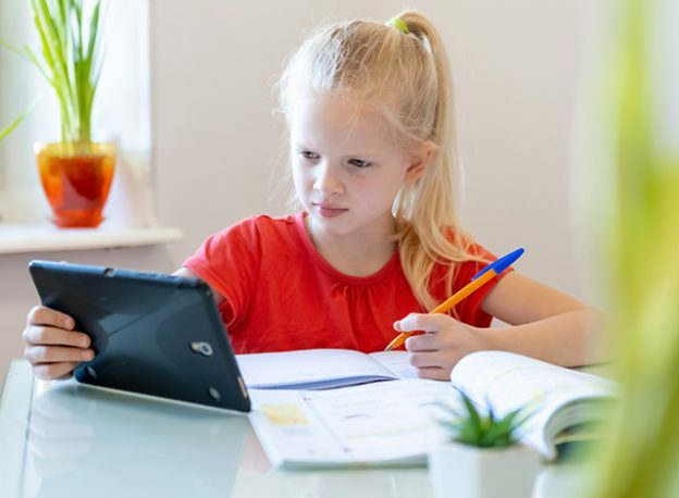 Young girl doing school work from home