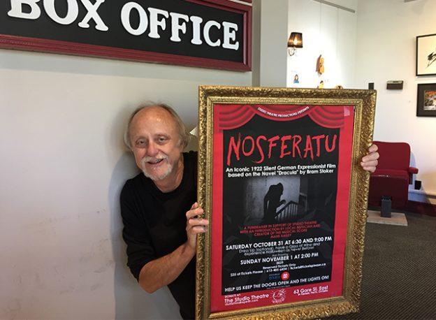 Perth musician and composer Mark Bailey holding a horror movie Nosferatu poster.
